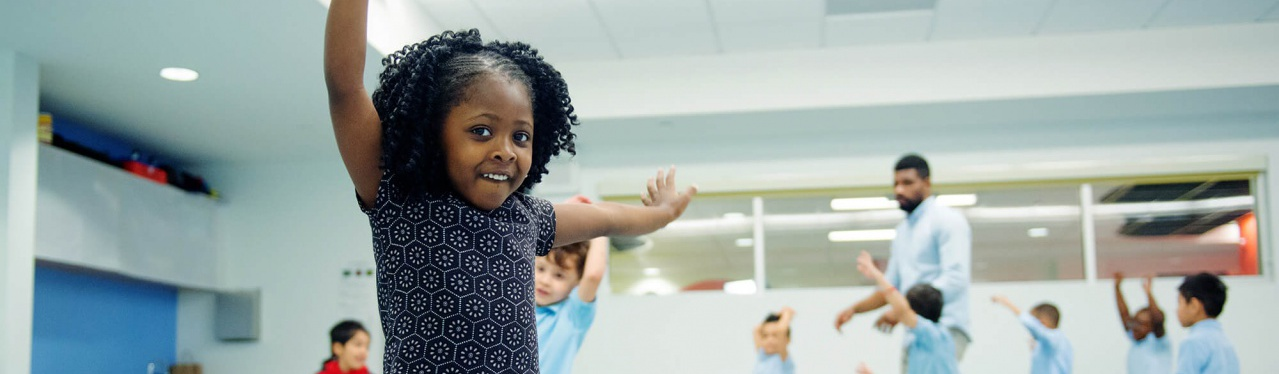 Photo-Kindermusik-PreK-BronxNY-AfricanAmerican-girl-dancing-hands-raised-smiling-6926x4622