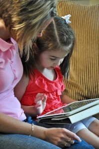 mom and young girl reading ebook together