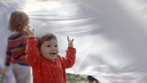 A child enjoys playing with a piece of cloth in the wind.